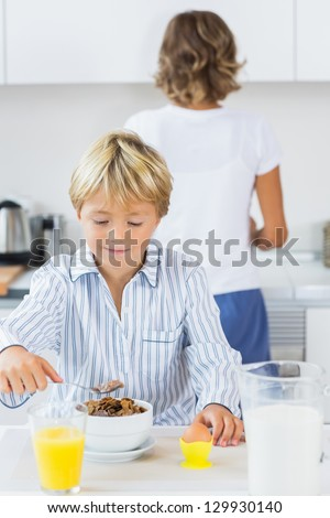 Young boy having breakfast in kitchen - stock photo