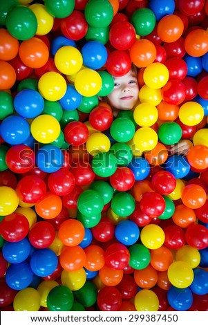 Young boy having fun and hiding in hundreds of colorful plastic balls - stock photo