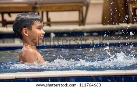 Young boy having fun in the swimming pool - stock photo