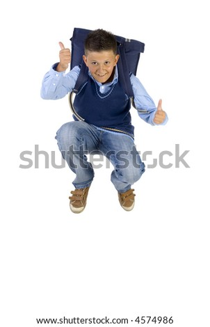 Young boy having fun. Jumping in the air with backpack. Looking at camera. Thumbs up. Isolated on white in studio, front view - stock photo
