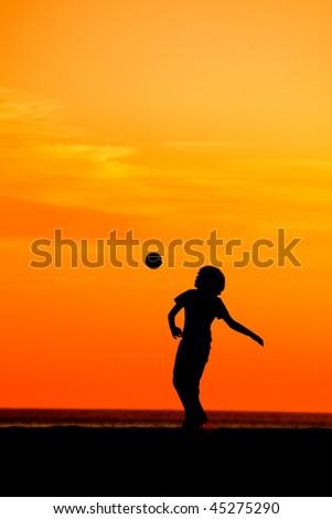Young boy having fun on the beach playing football - stock photo