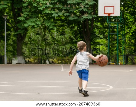 Young boy having fun playing basketball outdoors - stock photo