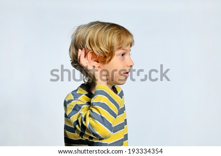 Young boy hear on gray background - stock photo