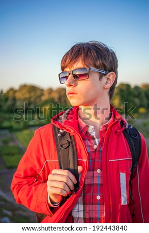 young boy hiker holding backpack and looking at the sunset