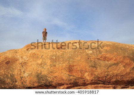 Young boy hiking on top of a boulder in the Utah desert, USA.