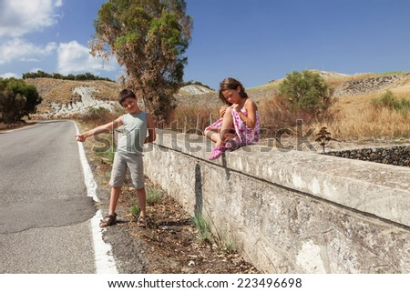 young boy hitchhiking along the street and young girl sits next him  - stock photo
