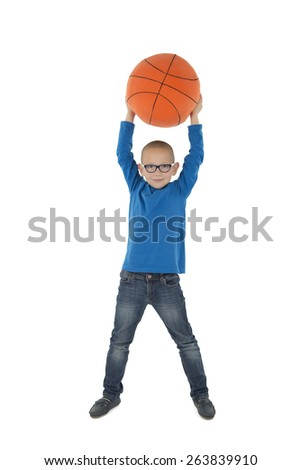 Young boy holding a basketball ball over his head against a white background - stock photo