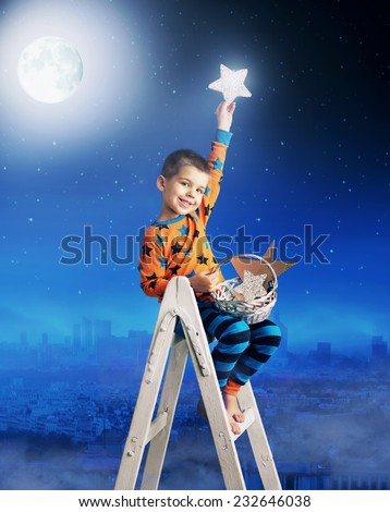 Young boy holding a bright star - stock photo
