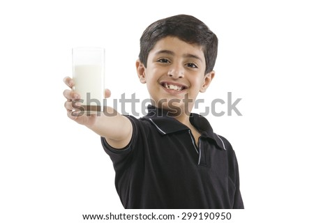 Young boy holding a glass of milk - stock photo