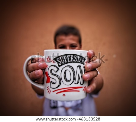 Young boy holding a mug with superstar son quote