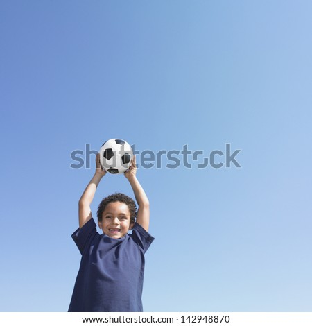 Young boy holding a soccer ball over his head