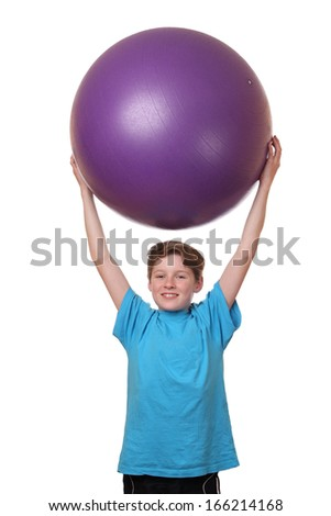 Young boy holding big pilates ball on his head on white background - stock photo