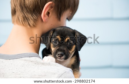 Young Boy Holding Black and Brown Puppy with Floppy Ears - stock photo