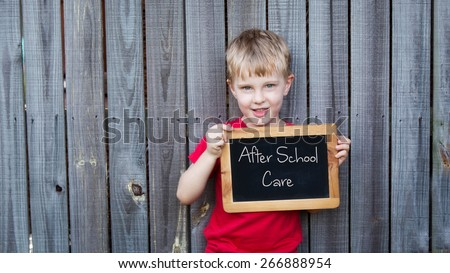 Young boy holding Blackboard advertising after school care - stock photo