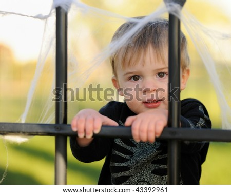 Young boy holding iron fence - stock photo
