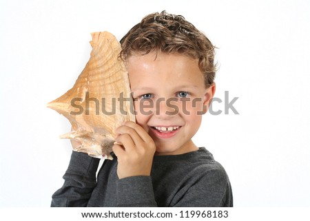 Young boy holding sea shell up and listening to the sounds of the ocean