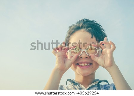 Young boy holding shell over sky background with vintage filter