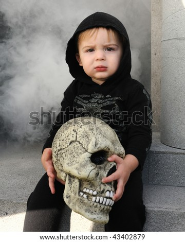 Young boy holding skull - stock photo