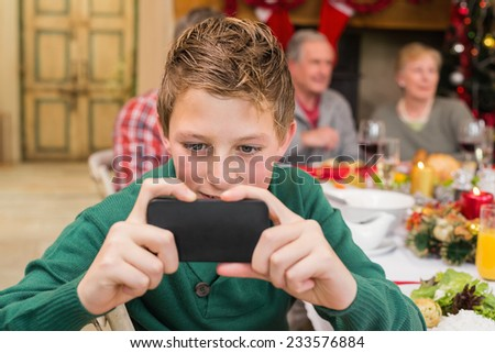 Young boy holding smartphone during christmas dinner at home in the living room - stock photo