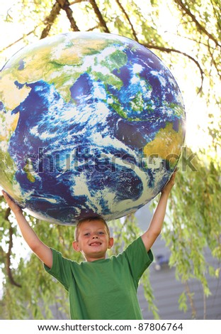 Young boy holding up large earth ball - stock photo