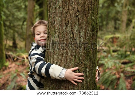 young boy hugging a tree - stock photo