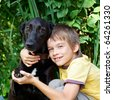 Young boy hugging  black dog outdoors - stock photo