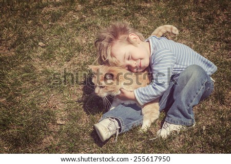 Young boy hugging his cat. Vintage instagram effect. - stock photo