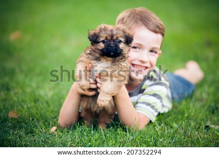 Young Boy Hugging his Dog - stock photo