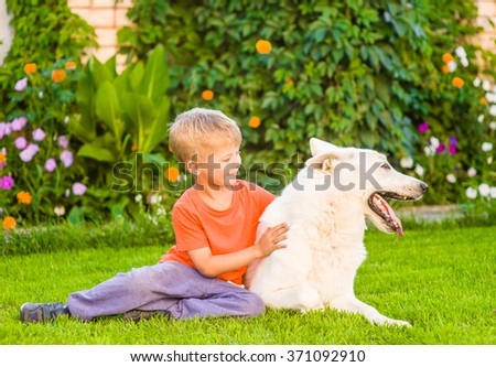 Young boy hugging White Swiss Shepherd dog together on green grass. - stock photo
