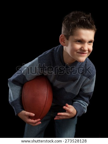 Young boy hunched over holding football.