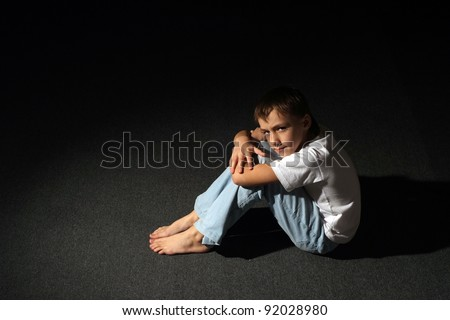 young boy in a dark room posing