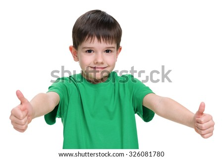 Young boy in a green shirt holds his thumbs up on the white background - stock photo