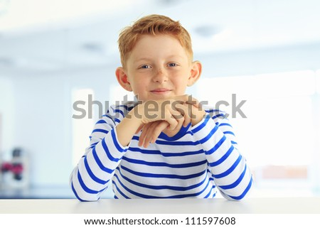 Young boy in a striped shirt sitting in classroom and smiles at the camera. Hands on his cheek. Horizontal shot. - stock photo