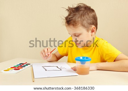 Young boy in a yellow shirt painting with watercolors - stock photo