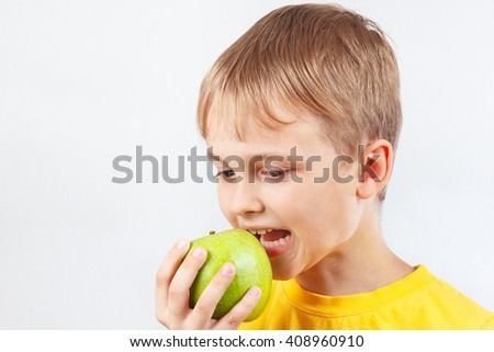 Young boy in a yellow shirt with green apple - stock photo