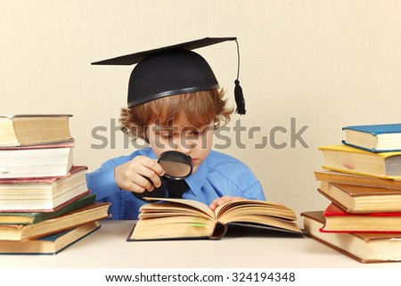 Young boy in academic hat studies an old books with a loupe - stock photo