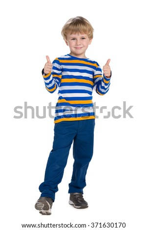 Young boy in blue pants holds his thumbs up on the white background - stock photo