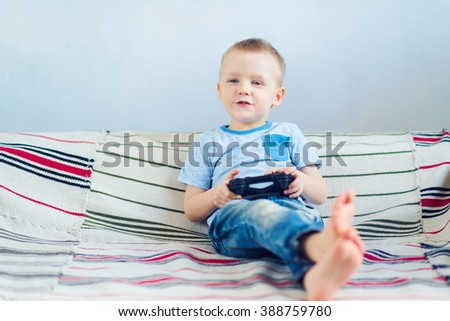 Young boy in blue t-shirt and jeans playing video games - stock photo