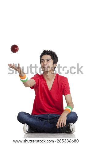 Young boy in casual wear tossing cricket ball while sitting cross-legged over white background