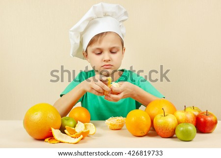 Young boy in chefs hat peeling fresh orange at the table with fruits