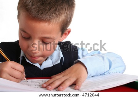 Young boy in elementary/primary school uniform working. Isolated. Copyspace - stock photo