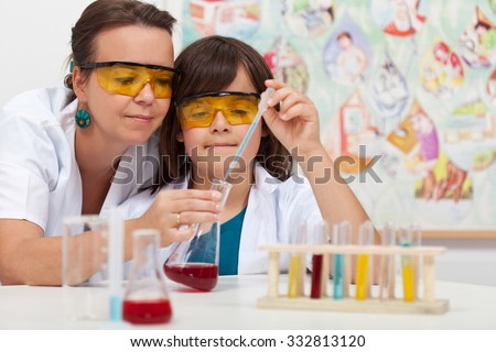 Young boy in elementary science class doing chemical experiment helped by teacher - stock photo