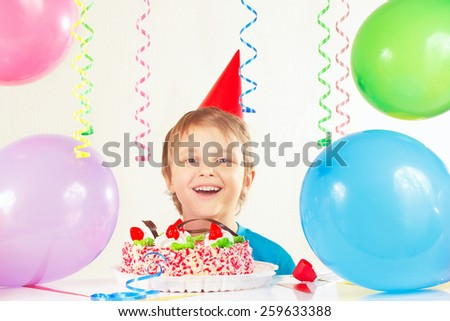 Young boy in festive hat with a birthday cake and balloons  - stock photo