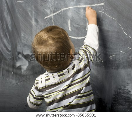 Young Boy in front of the blackboard - stock photo