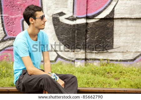 Young boy in glasses sitting at railway.