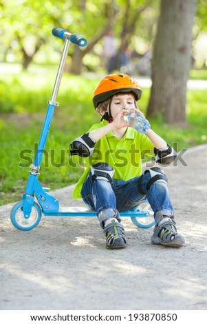 Young boy in green jacket drinks water from plastic bottle and sits on kick scooter - stock photo