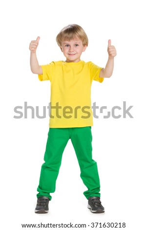 Young boy in green pants holds his thumbs up on the white background - stock photo
