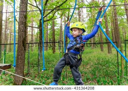 Young boy in helmet walks by rope at sunny summer day in adventure playground