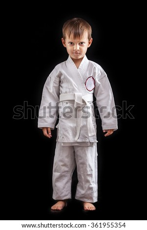 Young boy in kimono against black background - stock photo
