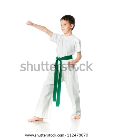 Young boy in kimono with green belt practising  on a white background - stock photo